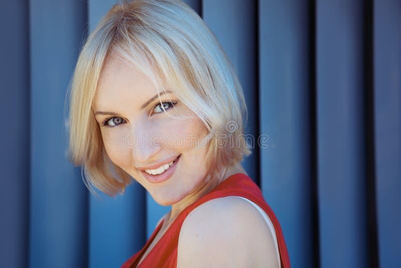 Blondine, die, angekleidet im roten sportwear lächeln Tag, im Freien stockfoto
