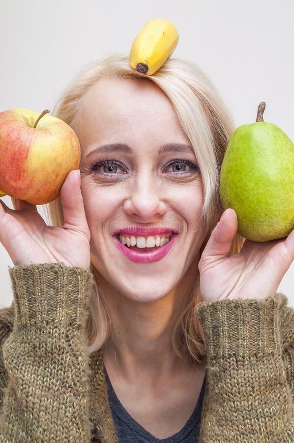 Blondine, die Apfel-, Birnen- und Bananenfrüchte halten stockfoto