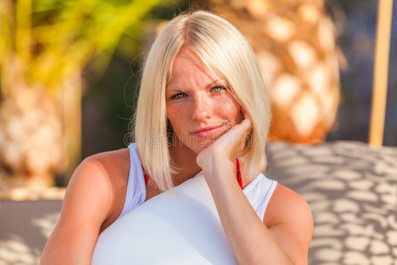 Blondine, die auf dem deckchair, Sommerferien genießend stationieren stockfoto