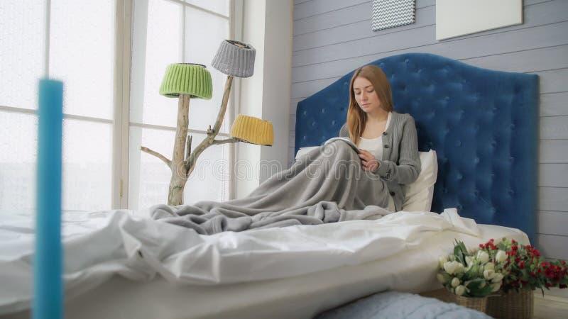 Blondine, die ein Buch beim Sitzen im Bett liest lizenzfreie stockfotografie
