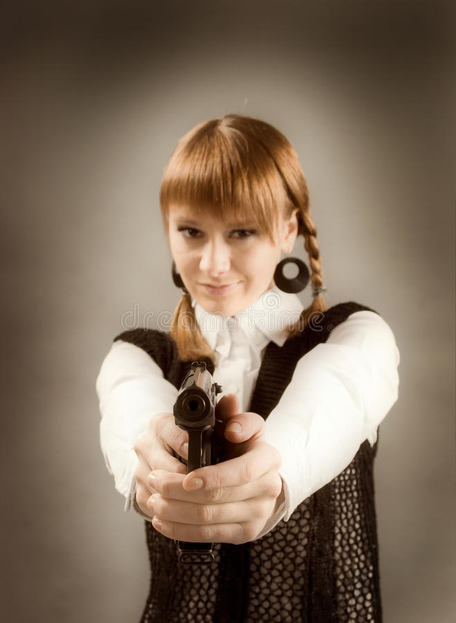 Blondine, die eine Gewehr anhält und in Richtung zur Kamera zielt lizenzfreie stockfotos