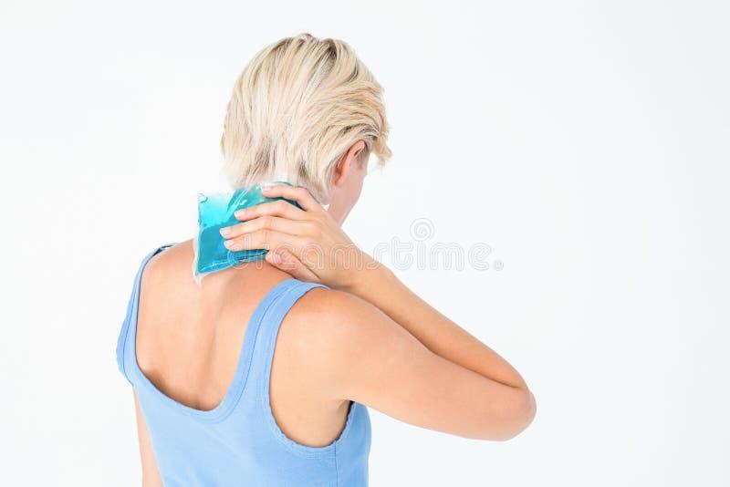 Blondine, die Gelsatz auf Hals setzen stockfotos