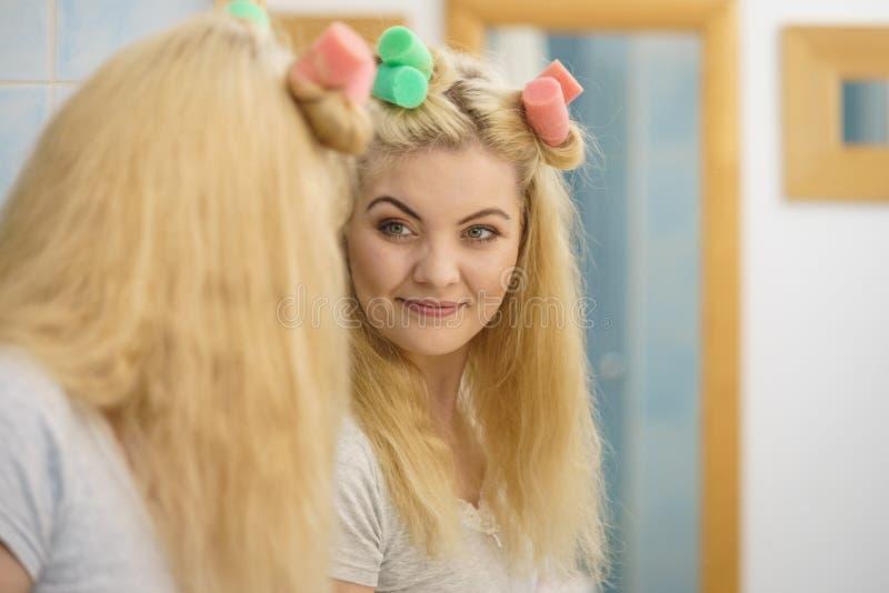 Blondine, die Haarrollen verwenden lizenzfreies stockfoto