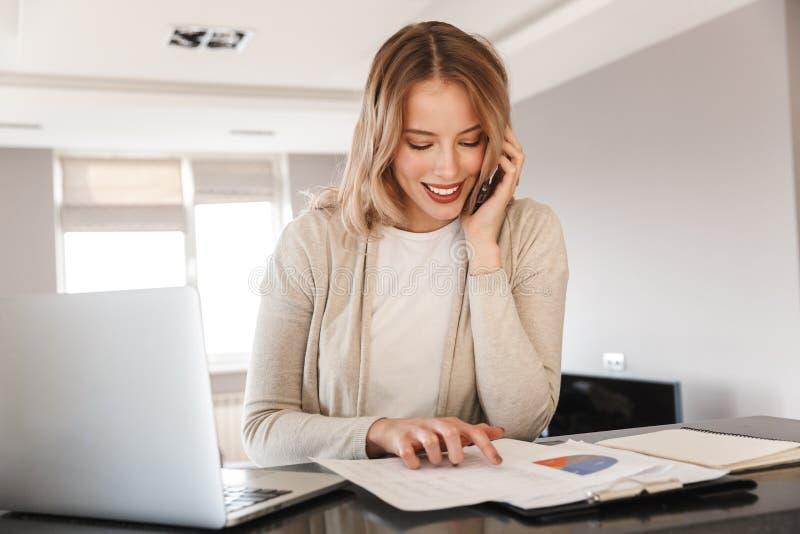 Blondine, die zuhause zu Hause sitzen unter Verwendung der Laptop-Computers spricht durch Handy aufwerfen stockfoto