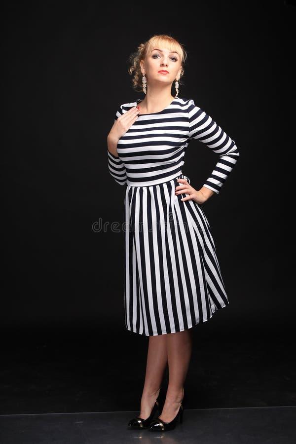 Blondine in einem gestreiften Kleiderspaß stockbild