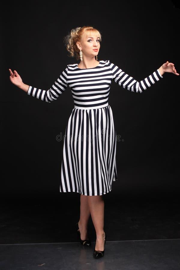 Blondine in einem gestreiften Kleiderspaß lizenzfreies stockbild