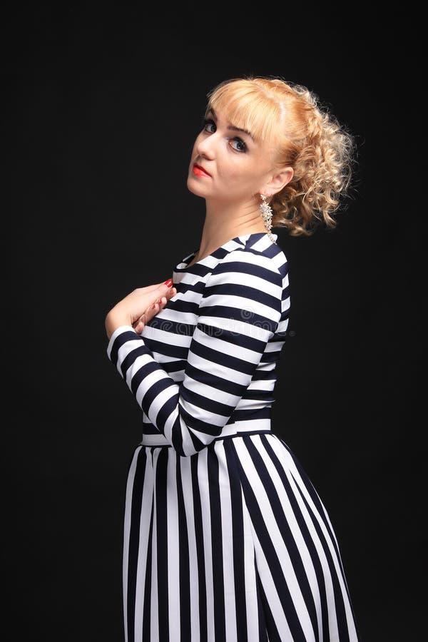 Blondine in einem gestreiften Kleiderspaß stockfotografie