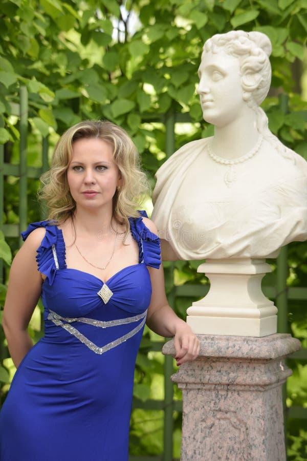 Blondine in einem sexy blauen Kleid im Park lizenzfreie stockbilder