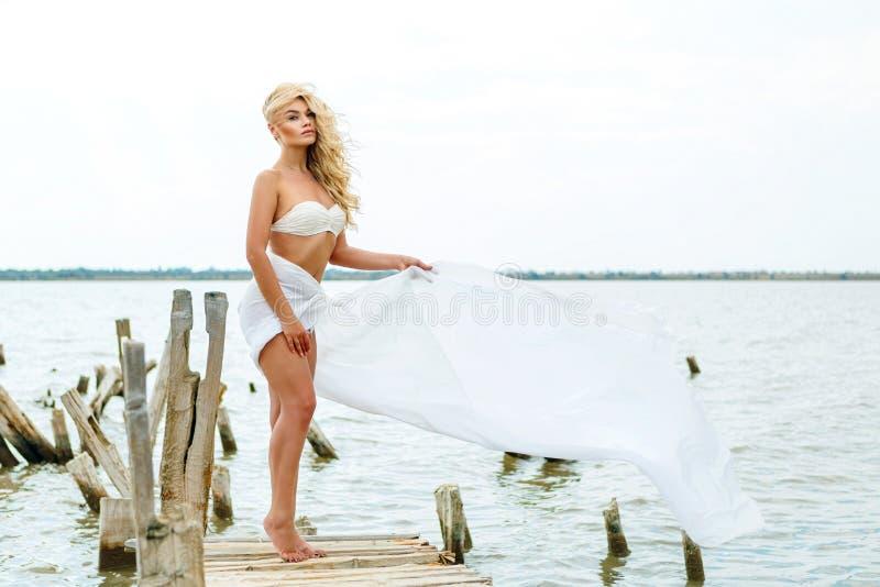 Blondine in einem weißen Badeanzug, stehend auf dem Hintergrund des Sees im Wind, Erholung stockfotos