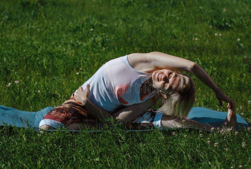 Blondine in einem wei?en T-Shirt auf dem gr?nen Gras, das Yoga tut Behandlung und Entspannung des Dorns Tr?gt Lebensstil zur Scha stockfotografie