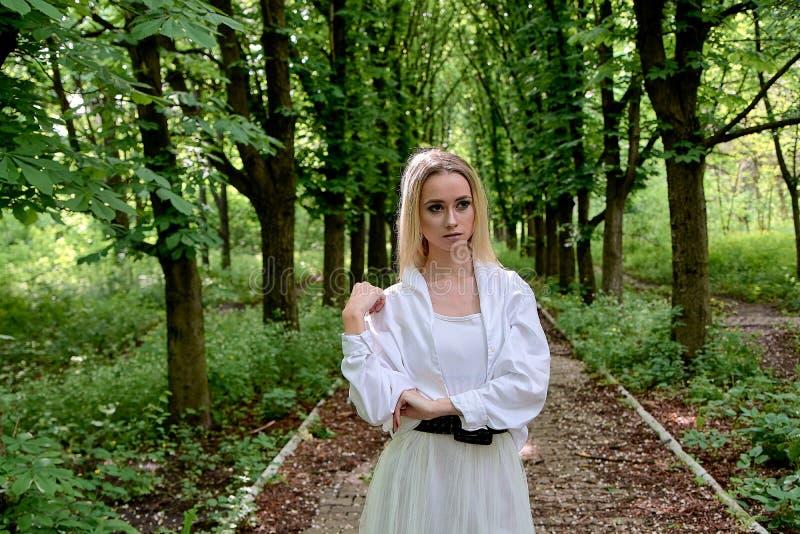Blondine gehen allein entlang die Kastaniengasse im Stadtpark r lizenzfreies stockfoto