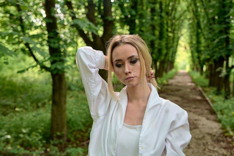 Blondine gehen allein entlang die Kastaniengasse im Stadtpark r stockbilder
