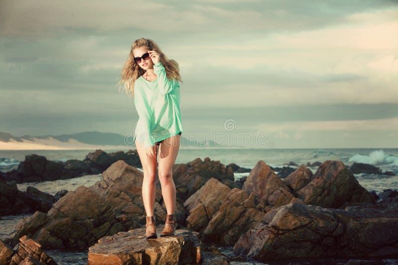 Blondine im grünen Trikot, das auf einem Felsen auf dem Strand steht stockbilder