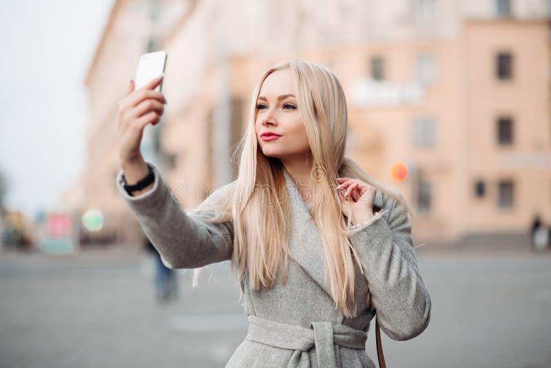 Blondine im grauen Mantel, der Selbstporträt an der Straße nimmt lizenzfreie stockfotografie