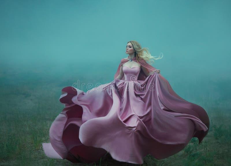 Blondine im Nebel in einem hellen langen teuren königlichen Kleid, das spontan flattert, nimmt die Gestalt einer magischen Blume, stockfotografie