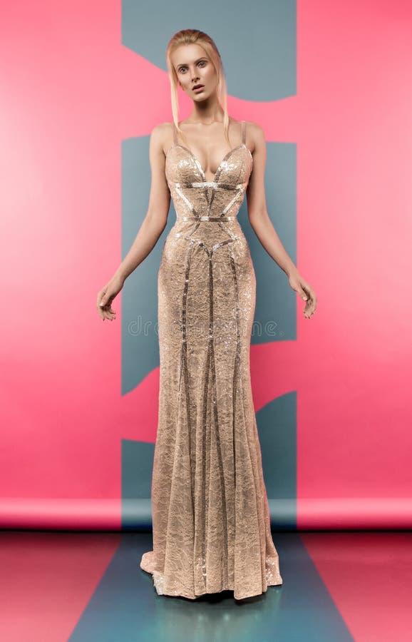 Blondine im schönen goldenen Kleid stockbild