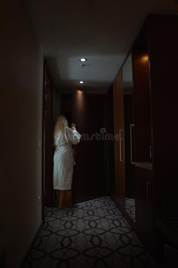 Blondine mit Bademantel öffnen eine Tür lizenzfreie stockfotos