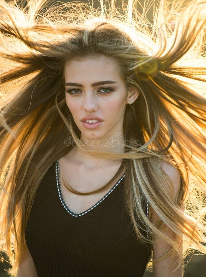 Blondine mit dem gelockten schönen Haar Schönheitsfriseursalon Stilvolle Franse Schönheitsmädchen mit dem langen und glänzenden g stockfotos