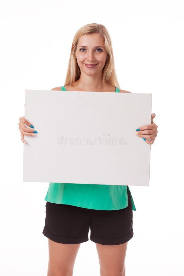 Blondine mit dem langen Haar, das mit weißer Platte aufwirft Setzen Sie ein Logo und annoncieren Foto auf einem weißen Hintergrun lizenzfreies stockbild