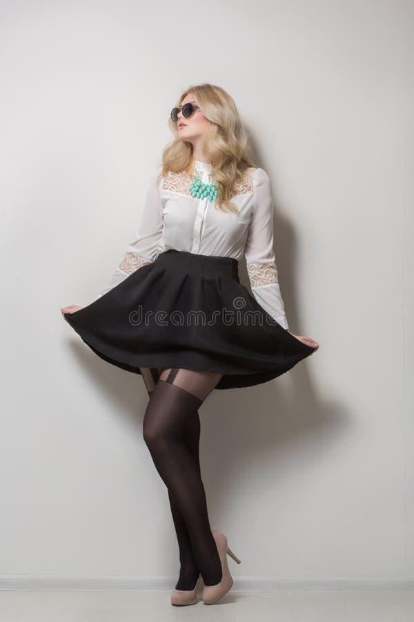 Blondine mit dem langen Haar in einem Rock Schwarze Sonnenbrillen lizenzfreies stockfoto