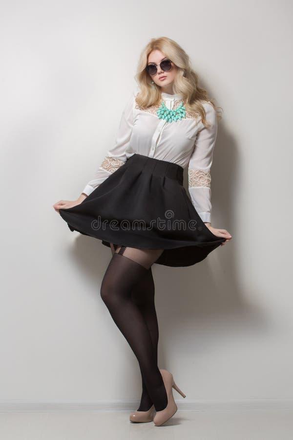 Blondine mit dem langen Haar in einem Rock Schwarze Sonnenbrillen lizenzfreie stockbilder