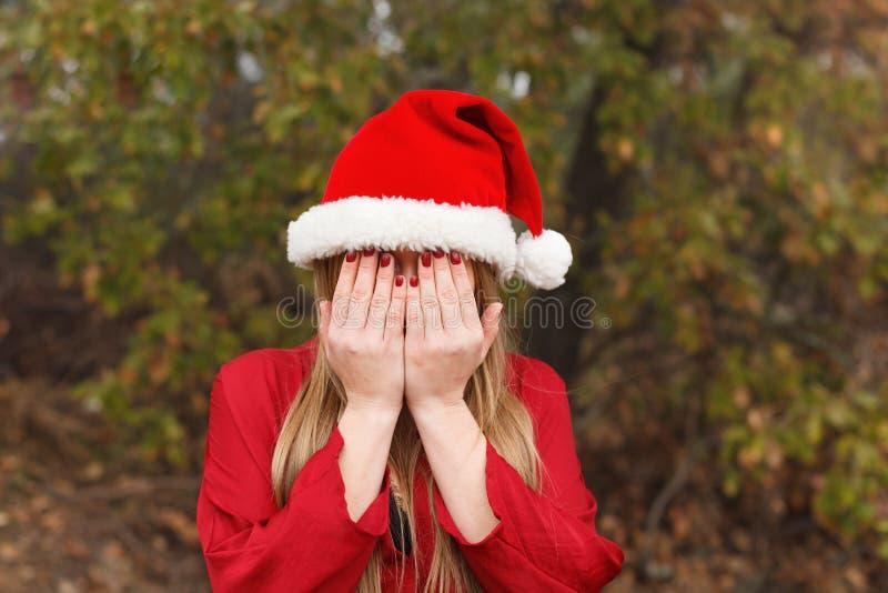Blondine mit dem Weihnachtshut, der ihr Gesicht bedeckt stockbilder