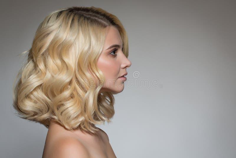 Blondine mit Locken auf einem grauen Hintergrund lizenzfreie stockfotografie