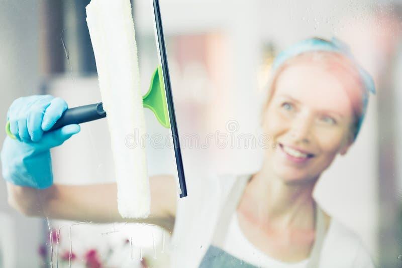 Blondine säubern Fenster lizenzfreies stockbild