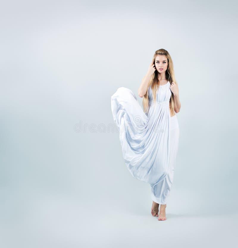 Blondine in wellenartig bewegendem weißem Kleid stockfotos