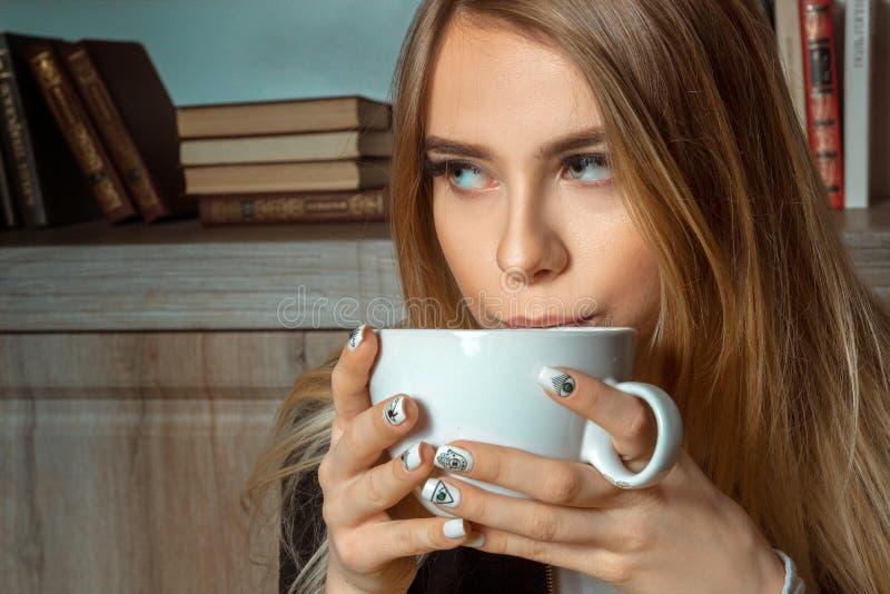 Blondinen dricker ett te royaltyfri fotografi