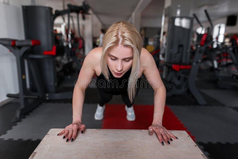 Blondinen för den unga kvinnan i sportig svart kläder utbildar i idrottshallen Flickan gör övningar för händer i konditionstudio royaltyfria foton