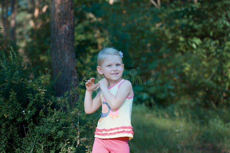 Blondinen för det lilla barnet rätar ut hennes hår och le royaltyfri bild