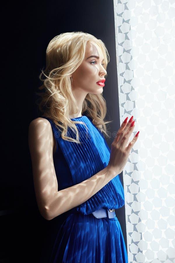 Blondinen i blått klär anseende på fönstret, kvinnanedgångskugga av gardinerna Härlig sinnlig stående av en mystisk flicka royaltyfri bild