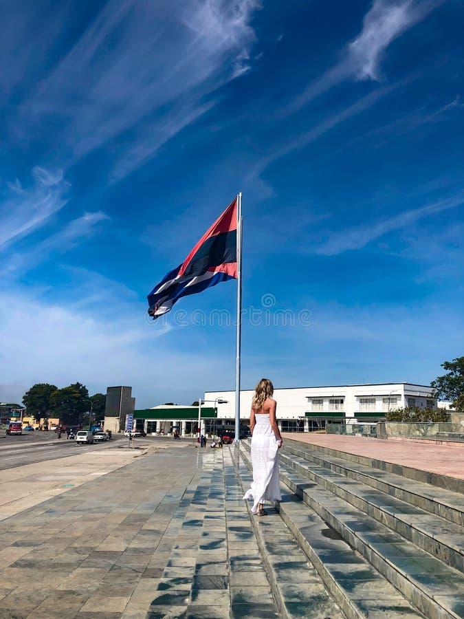 Blondinen klättrar trappan bredvid flaggan av Kuban royaltyfri bild