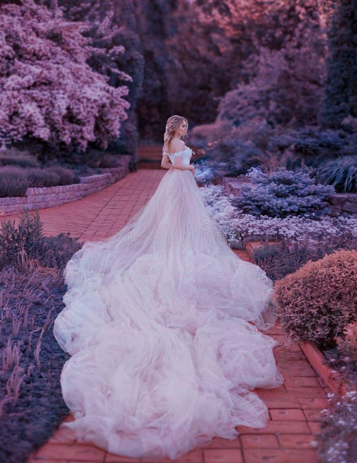 Blondinen med en härlig elegant frisyr, går i en sagolik blommande trädgård Prinsessa i ett lyxigt ljus - rosa färger klär arkivfoton