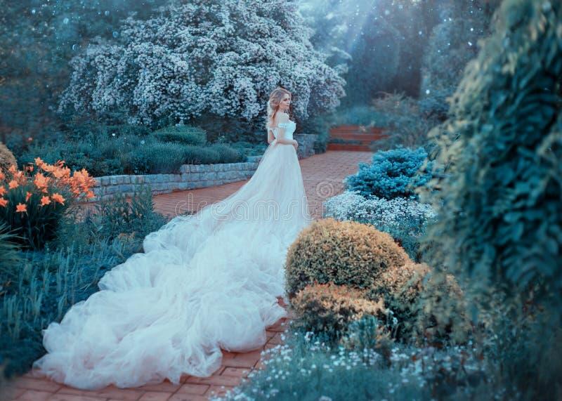 Blondinen med en härlig elegant frisyr, går i en sagolik blommande trädgård Prinsessa i ett lyxigt ljus - rosa färger klär royaltyfri bild