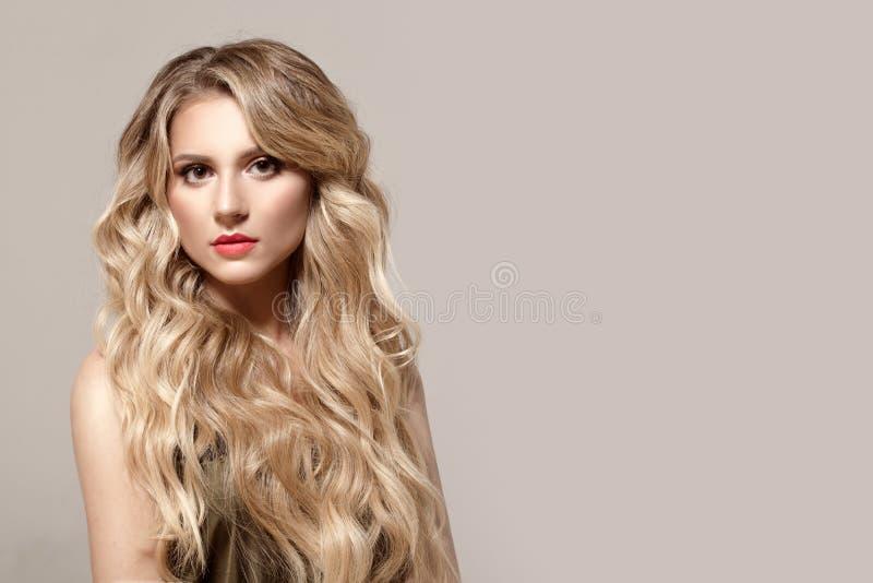 Blondinen med krullning på en grå bakgrund, det naturliga sminket och rengöringen flår hår long royaltyfria bilder
