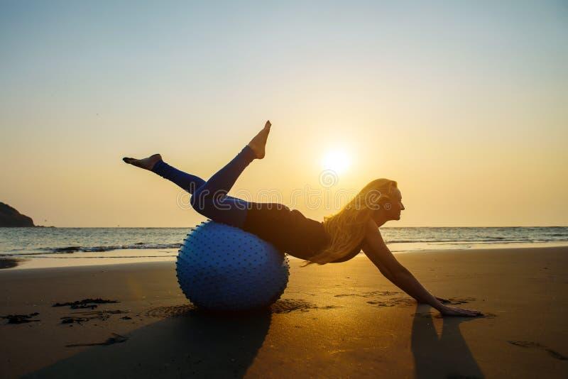 Blondinen med långt hår gör Pilates på stranden under solnedgång mot havet Ung böjlig lycklig kvinna som gör konditionövningar royaltyfri bild