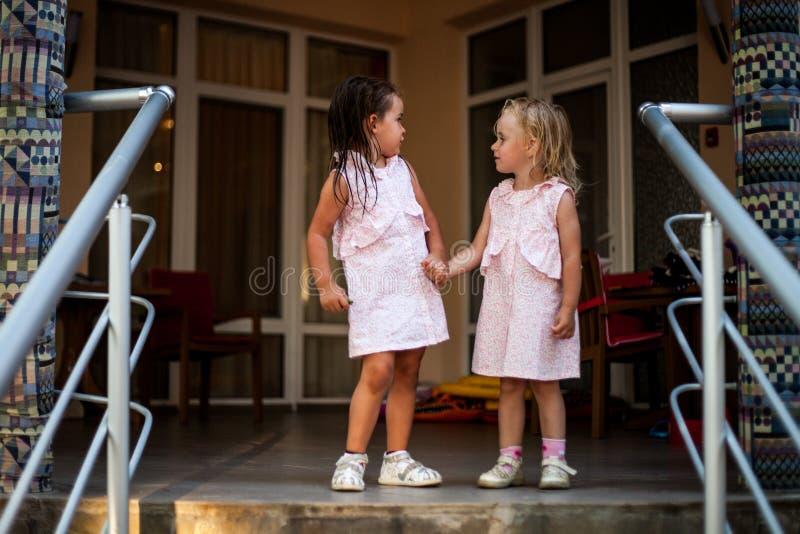 Blondinen och brunetten för två systrar behandla som ett barn flickor i de samma klänningarna som rymmer händer royaltyfri bild