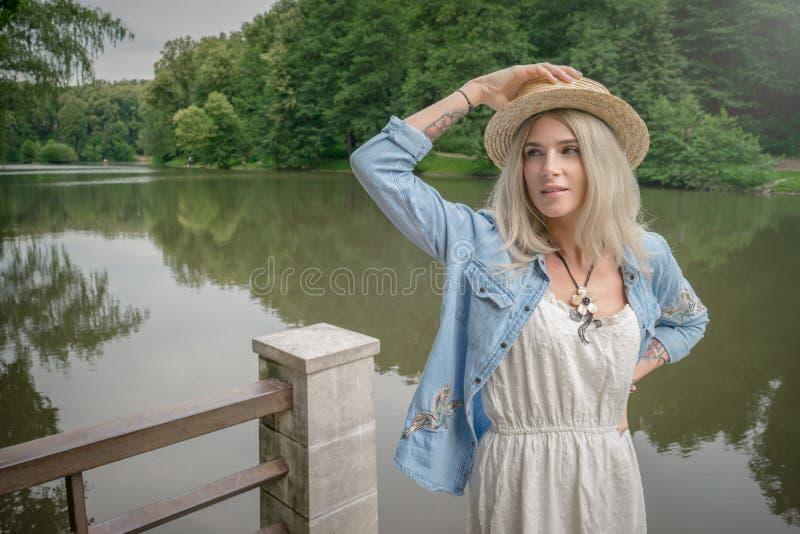 Blondinen rymmer en sugrörhatt på hennes hand och står på kanten av en stenpir i en vit klänning och en blå grov bomullstvillskjo arkivbild