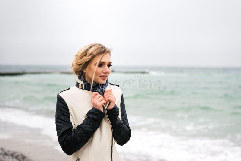 Blondinen står på bakgrunden av havet och ser bort arkivbilder