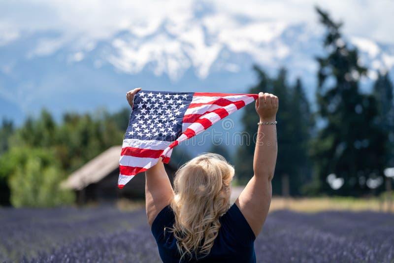 Blondinestellung auf einem Gebiet des Lavendels nahe Mt Haube hält einen Amerikaner Fiag, während sie im Wind durchbrennt Konzept stockfotografie
