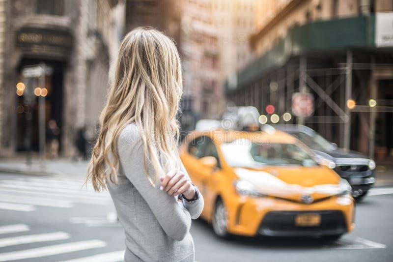 Blondinestellung auf Stadtstraße und Wartetaxiauto am sonnigen Tag stockbilder