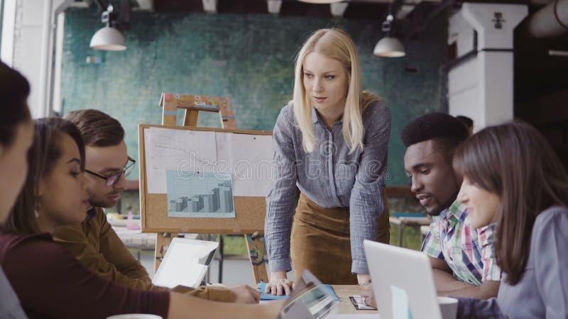 Blondineteamleiter, der dem Mischrasseteam von jungen Kerlen Richtung gibt Kreatives Geschäftstreffen im modernen Büro lizenzfreie stockfotografie