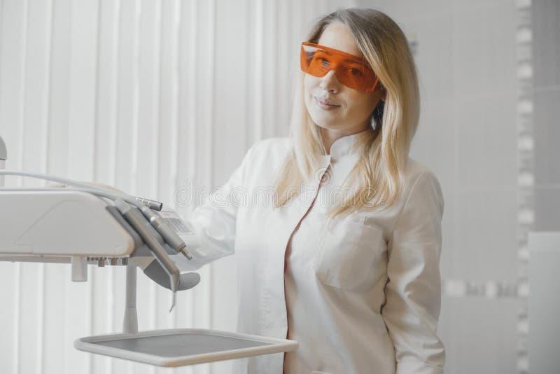 Blondinezahnarzt, der nahe bei zahnmedizinischer Ausrüstung in der Stomatologie steht lizenzfreie stockbilder