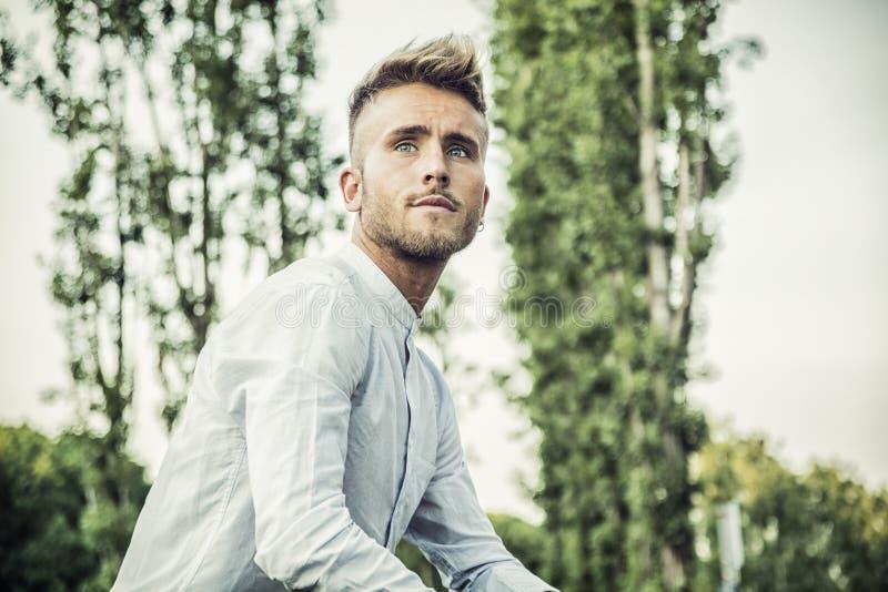 Blondish, синь наблюдала молодой человек в парке стоковое фото rf