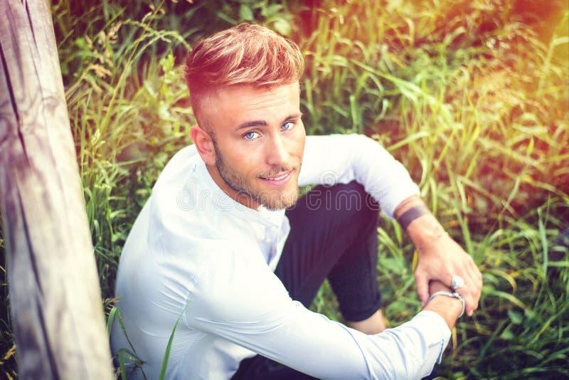 Blondish, синь наблюдала молодой человек на деревянной загородке стоковое изображение rf