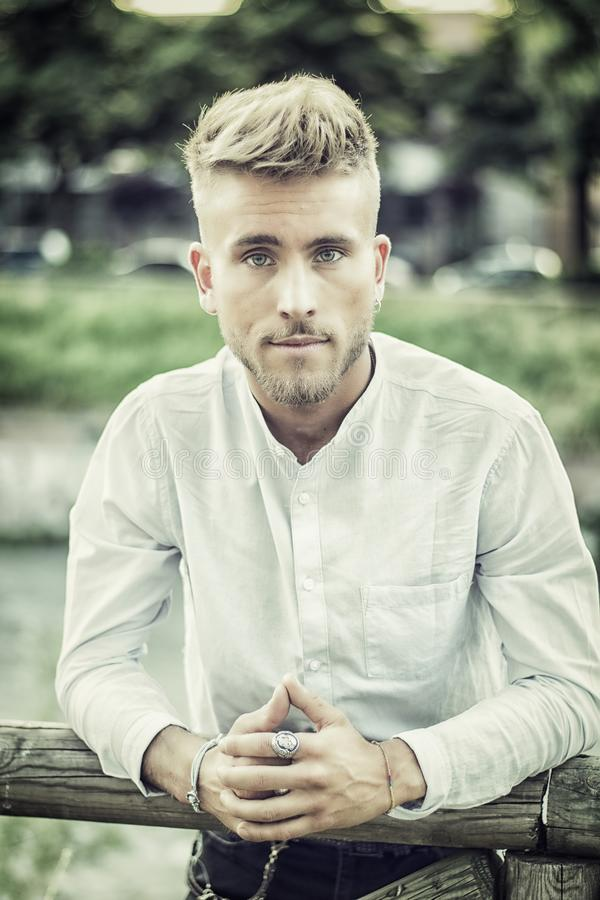 Blondish, синь наблюдала молодой человек усмехаться реки стоковое изображение