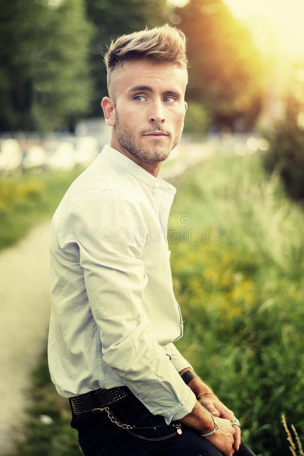 Blondish blå synad ung man på det wood staketet arkivfoton