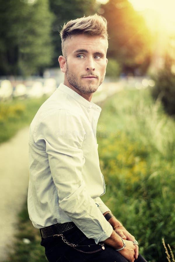 Blondish, blauwe eyed jonge mens op houten omheining stock foto's